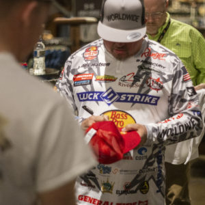 Major League Fishing pro James Watson signs a fan's hat.