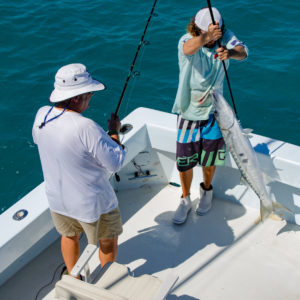 Fishing guide Dallas helps one of the Ultimate Dream winners boat a huge barracuda. Photo by Rachel Dubrovin.