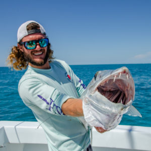 Fishing guide Dallas shows off the barracuda's teeth. Photo by Rachel Dubrovin.