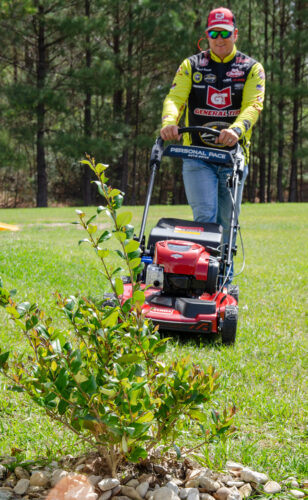 Skeet Reese using the Toro walk-behind mower to trim up the front yard. Photo by Rachel Dubrovin