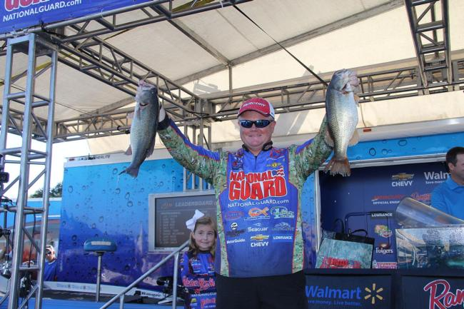 With daughter Hannah Grace peeking from behind, National Guard pro Mark Rose shows off two of his winning fish.